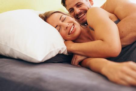 couple sleeping: Feliz pareja joven abrazando mientras está acostado junto a la otra en la cama. Caucásica pareja sonriente en la cama juntos. Pareja despertarse. Foto de archivo