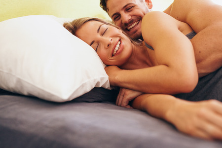 Happy young couple embracing while lying next to each other on bed. Caucasian couple smiling in bed together. Couple waking up. Stock Photo