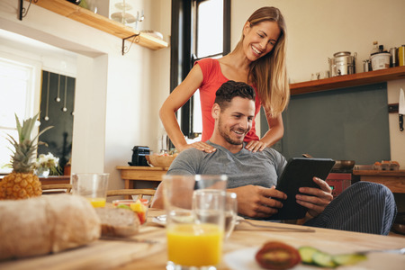 Shot van de gelukkige jonge man en vrouw met behulp van digitale tablet in de ochtend. Echtpaar met behulp van touchpad in de keuken lachend. Stockfoto