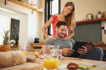 Tiro do homem novo feliz e mulher que usa a tabuleta digital no manhã. Pares usando o touchpad na cozinha sorrindo.