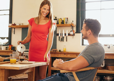 a jar stand: Couple in kitchen at breakfast table. Young woman serving coffee to her boyfriend sitting on chair. Young couple looking at each other and smiling.