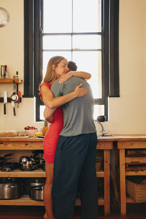 love hug: Young couple in love hugging each other. Young man and woman in kitchen embracing. Stock Photo