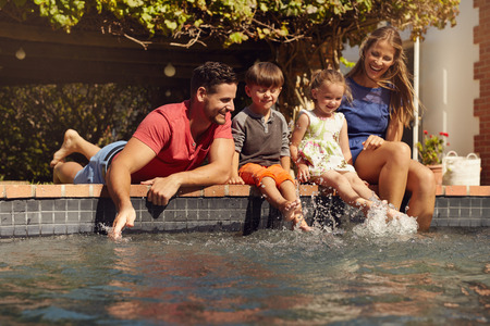 pool fun: Caucasian family having fun by their swimming pool. Happy young family splashing water with hands and legs while sitting on edge of swimming pool. Kids with parents playing outdoors. Stock Photo
