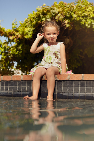Outdoor shot of a little girl dipping her feet in the pool. Cute little girl sitting on the edge of a swimming pool looking at camera on a bright sunny day. photo