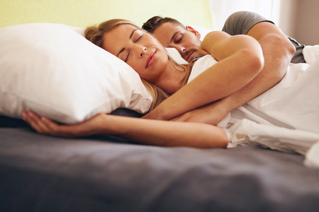 the laying: Image of a young couple together sleeping comfortably on the bed. Young man and woman lying asleep.