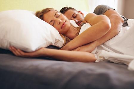 pareja durmiendo: Imagen de una joven pareja juntos dormir c�modamente en la cama. Hombre joven y mujer durmiendo.
