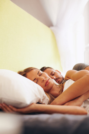 couple sleeping: Tiro de interior de hombre y una mujer durmiendo juntos en el dormitorio. Pareja caucásica joven que duerme en la cama.