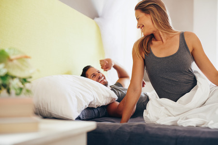 Happy young couple waking up in the morning on bed. Caucasian man and woman looking at each other smiling.