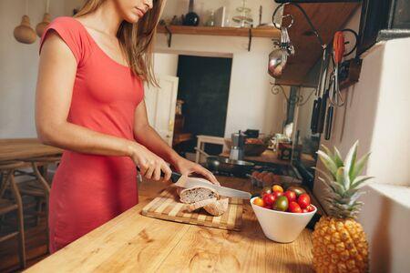 haciendo pan: Recortar foto de una mujer joven que rebana un pan recién horneado de pan en un mostrador de la cocina doméstica. Mujer desayuno de la mañana decisiones. Foto de archivo