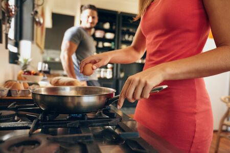 Closeup image of woman cracking an egg into a frying pan with man standing in background in kitchen. Preparing breakfast. photo