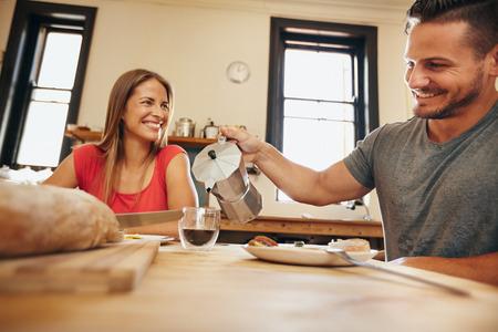 그의 여자 친구 집에서 부엌에서 아침 식사와 함께 컵에 커피를 붓는 젊은 남자의 실내 촬영. 젊은 부부 아침 식사를 웃고.
