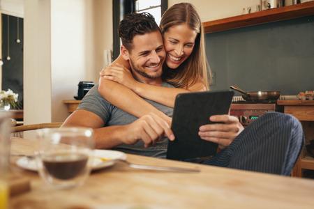 彼らは台所で朝一緒にタブレット コンピューターを読んで笑顔のカップル。若い男性と女性の社会的なメディアの笑顔に追いつきます。保持してい