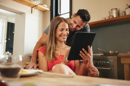 modern home: Couple smiling using a tablet computer together in morning at kitchen. Young man and woman at breakfast table using digital tablet.