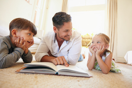 Indoor shot of young man with two kids reading a story book . Family lying on the floor with a book in living room.