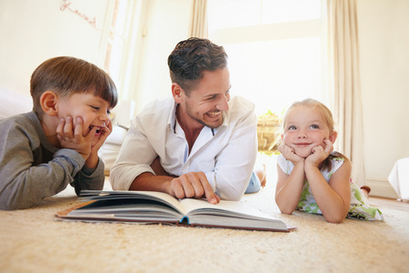 two story: Portrait of happy young family of three lying on floor with a book. Father with two kids reading a story book in living room at home. Stock Photo
