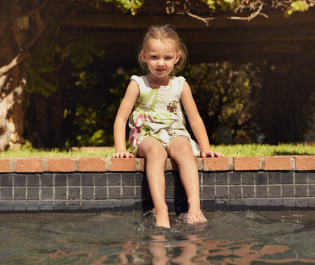 only one girl: Adorable little girl enjoying sitting by edge of pool on sunny day. Young girl with her feet in swimming pool looking at camera. Stock Photo