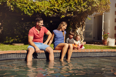 Happy young couple sitting on the edge of swimming pool with their kids enjoying a hot summer day near pool. Couple's feet in water and kids playing by outdoors.