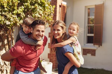 Gelukkige vader en moeder kijken naar de camera terwijl het meeliften hun zoon en dochter. Gelukkig jong gezin van vier spelen in hun achtertuin op een zonnige dag. Stockfoto