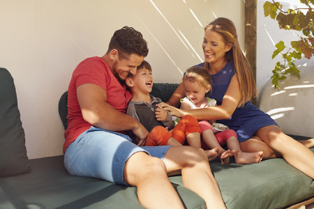 Shot of happy family of four in their backyard having fun, sitting on couch playing. Parents playing with kids laughing in patio.