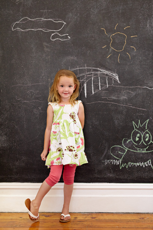Full length portrait of innocent little girl standing at home looking at camera, against a black wall with chalk drawings.