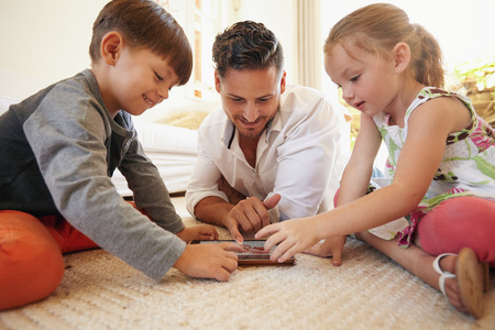 computer use: Father with son and daughter sitting on floor using digital tablet indoors. Happy young family together at home using touchpad computer. Young man teaching his children how to use digital tablet.
