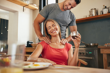 massage: Happy junge Frau sitzt am Frühstücks Tablette holding Tasse Kaffee, die eine Schultermassage von ihrem Freund. Junge Paare in der Morgen mit Freund reiben Schultern Freundinnen in der Küche.
