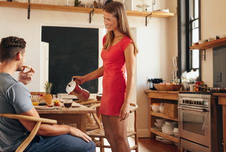Tiro de interior de la pareja tomando el desayuno en la cocina doméstica. Mujer joven de pie y servir el café con el hombre sentado en la silla de comer pan.