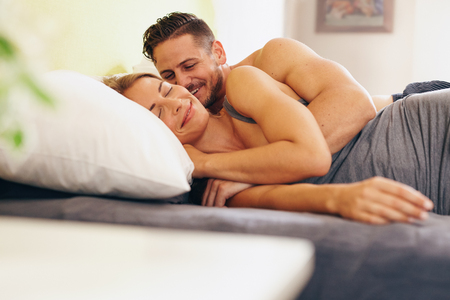 Enamored young couple lying on bed together in the bedroom. Happy man and woman waking up in morning. Stock Photo