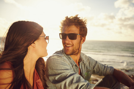 Close-up portrait of loving young couple looking at each other at the beach. Romantic caucasian couple in love on summer holiday.