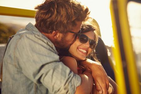 Jonge man omhelzen en kussen zijn mooie vriendin, terwijl op een road trip. Romantisch paar in een auto op zomervakantie.