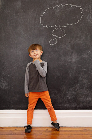 Child thinking with a thought bubble on the blackboard. Full length shot of cute little boy standing at home. Inspiration and solution concept.