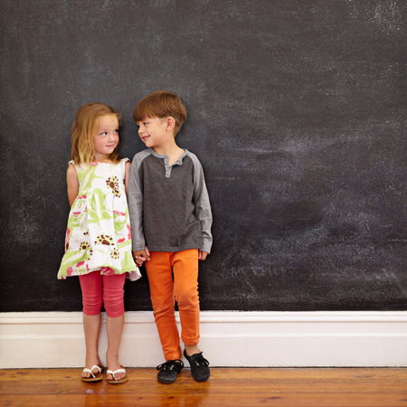 each: Little boy and girl standing in front of blackboard looking at each other. Indoors shot of children at home with copy space.