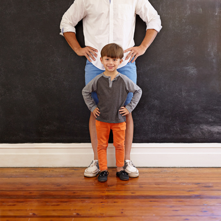 lookalike: Indoor shot of little boy and his father standing with their hands on hips. Little boy in front smiling and his father is cropped in the picture.