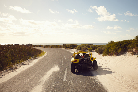 open topped: Rear view of young couple driving down a open road to the beach on a sunny day. Couple on road trip in a small car. Stock Photo