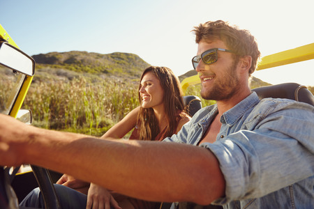 drives: Young friends out for a drive together in a open topped car. Couple on road trip in a car. Stock Photo