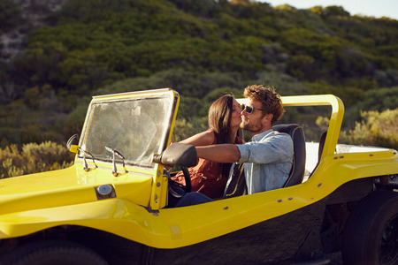 Affectionate young couple on a roadtrip. Man driving buggy car being kissed by his girlfriend.