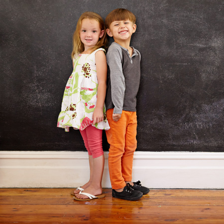 together standing: Little boy and girl standing back to back in front of blackboard looking at camera smiling. Full length image of two innocent little children together at home. Stock Photo