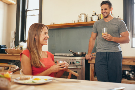 2 people at home: Shot of young couple in kitchen smiling. Young woman sitting at breakfast table with man standing by kitchen counter holding a glass of juice. Stock Photo