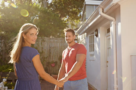 causal: Portrait of beautiful young woman holding hand of her boyfriend and looking at camera. Young couple outdoors in their backyard on a sunny day. Stock Photo