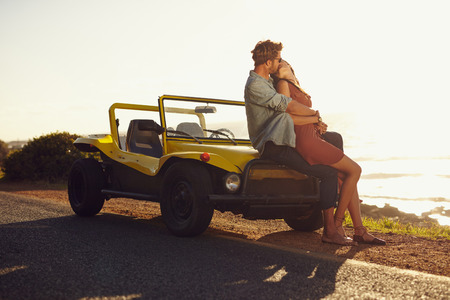 passionate kiss: Romantic young couple sitting on hood of their car and kissing. Young couple sharing a passionate kiss on road trip. Car parked alongside road with affectionate couple.