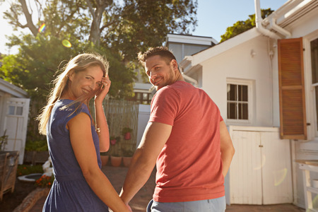 Rear view shot of a young couple taking a walk around their house holding hands. Loving young couple outdoors in their backyard on a bright sunny day looking back at camera smiling.