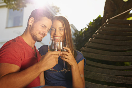 Outdoor shot of young caucasian couple in backyard toasting wine smiling. Romantic couple relaxing on hammock celebrating with wine.