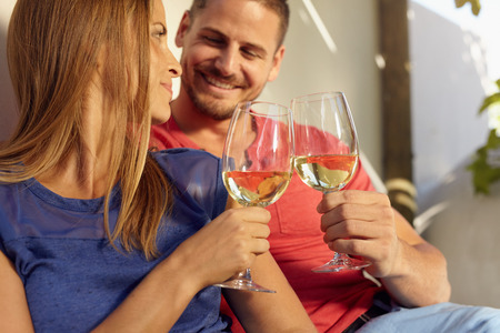 toasting wine: Closeup shot of young man and woman sitting together toasting wine glasses. Couple in love spending romantic time together. Stock Photo