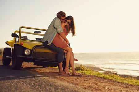 ロマンチックな若いカップル屋外特別な瞬間を共有します。道路の旅行に愛の若いカップル。自然の中に自分の車のボンネットに座って抱き合って