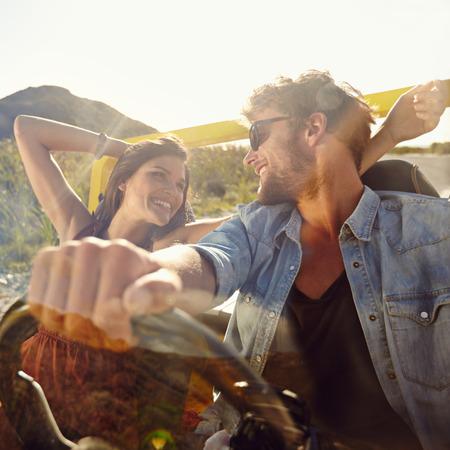 Gelukkig jonge man en vrouw in een auto te genieten van een road trip op een zomerse dag. Paar op een schijf in een open auto. Stockfoto