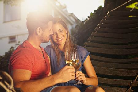 backyard woman: Beautiful young couple toasting wine outdoors. They are sitting on a hammock smiling and drinking wine with bright sunlight in backyard. Young man and woman spending quality time together on weekend.