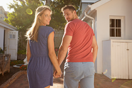 looking over shoulder: Shot of young couple in backyard on a bright sunny day. They are walking to their house hand in hand, looking over their shoulders at the camera.