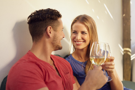 backyard woman: Happy young man and woman enjoying a glass of wine in their backyard. Couple toasting wine and looking at each other smiling. Stock Photo