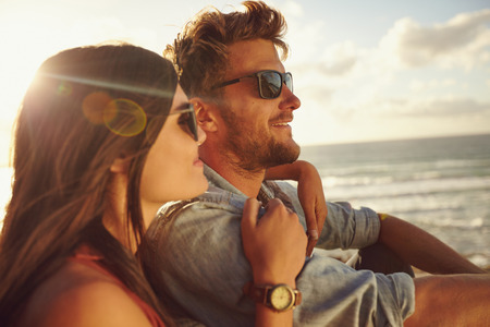 sea side: Romantic young couple together outdoors on a summer day. Caucasian couple enjoying the beach view. Stock Photo