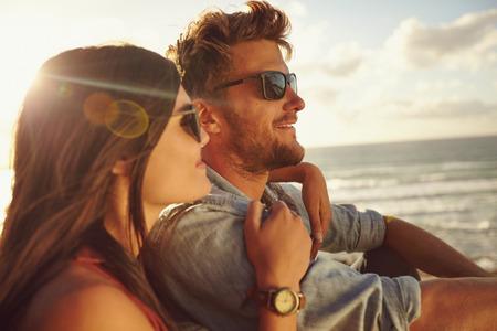 Romantique jeune couple ensemble à l'extérieur sur une journée d'été. Caucasien couple profitant de la vue sur la plage.